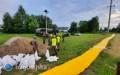 Strażacy rozkładają rękaw przeciwpowodziowy nad zalewem